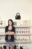 站立与胳膊的一名愉快的中间妇女的画象在鞋店横渡了 库存照片