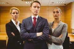 站立与胳膊的三位严肃的律师横渡 免版税图库摄影