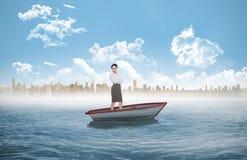 站立与胳膊的典雅的女实业家的综合图象在风船横渡了 免版税图库摄影