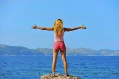 站立与胳膊的可爱的妇女对空气打开自由在海前面 免版税库存照片