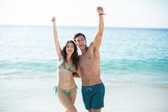 站立与胳膊的夫妇被举在海滩 免版税库存照片