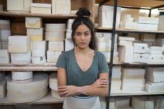 站立与胳膊的女性陶瓷工在瓦器车间横渡了 库存照片