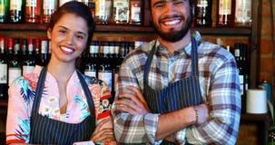 站立与胳膊的女服务员和男服务员画象横渡了在酒吧柜台
