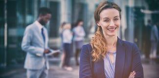 站立与胳膊的微笑的女实业家横渡 库存图片