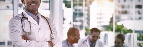 站立与胳膊的愉快的医生画象横渡,当他的同事工作时 免版税图库摄影