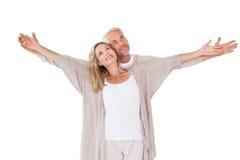 站立与胳膊的愉快的夫妇被伸出 免版税库存图片