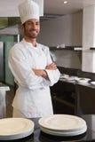 站立与胳膊的愉快的主厨在柜台后横渡了 免版税库存照片