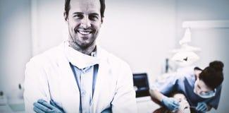 站立与胳膊的牙医横渡在诊所 免版税库存照片