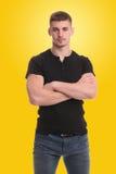 站立与胳膊的英俊的年轻人重叠了黄色背景 免版税库存图片