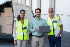 站立与膝上型计算机和剪贴板的经理和仓库工作者 免版税图库摄影