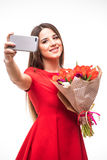 站立与色的郁金香花束的微笑的女孩在他们的手上,在白色做selfie电话 库存照片