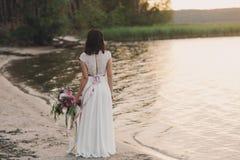 站立与花束的新娘根据日落 免版税库存照片