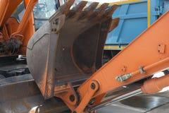 站立与被降下的桶的挖掘机 免版税库存图片