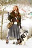 站立与西伯利亚爱斯基摩人狗的愉快的少妇 图库摄影