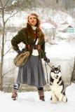 站立与西伯利亚爱斯基摩人狗的愉快的少妇 库存图片