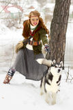 站立与西伯利亚爱斯基摩人狗的愉快的少妇 库存照片