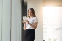 站立与计算机片剂的少妇在手上 免版税库存照片
