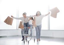 站立与购物车的一个年轻家庭的全长画象 图库摄影
