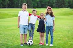 站立与足球和微笑对照相机的不同种族的孩子在公园 免版税库存照片