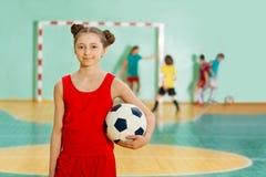 站立与足球的女孩在比赛期间 免版税库存照片
