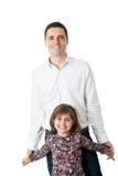 站立与逗人喜爱的矮小的女儿的年轻英俊的人 图库摄影