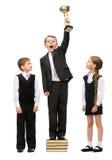 站立与金杯子的男孩在堆书在其他孩子中 库存图片