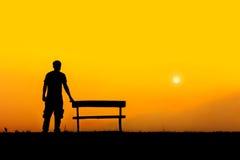 站立与长凳的人剪影 免版税图库摄影