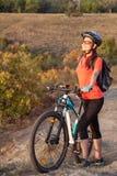 站立与闭合的眼睛和en的成人可爱的女性骑自行车者 免版税库存图片