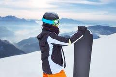 站立与雪板在一只手上和享受高山山风景-雪板运动概念的女性挡雪板 免版税图库摄影