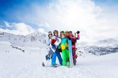 站立与雪板的五个朋友 库存图片