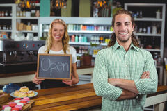站立与顾客的微笑的女服务员拿着有开放标志的黑板 库存照片