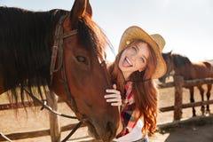 站立与马和显示舌头的快乐的妇女女牛仔 免版税库存照片