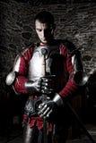 站立与头低下在祷告和拿着金属剑的勇敢的骑士对石墙 库存照片