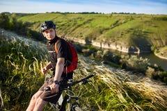 站立与登山车的可爱的骑自行车者反对美好的风景 库存图片