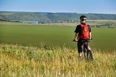 站立与登山车的骑自行车者的背面图反对美好的风景 库存图片