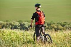 站立与登山车的骑自行车者的背面图反对美好的风景 免版税库存照片