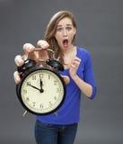 站立与紧张最后期限的一个时钟的害怕的美丽的少妇 免版税库存照片