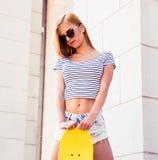 站立与滑板的女性少年 免版税库存图片