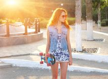 站立与滑板的美丽的少妇在她的手上 库存照片