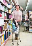站立与购物车和选择的微笑的妇女物品 免版税图库摄影