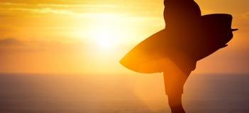 站立与他的在海滩的冲浪板的冲浪者在海洋的日落 图库摄影