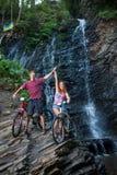 站立与他们的自行车的年轻夫妇近的瀑布 免版税库存图片