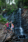 站立与他们的自行车的年轻夫妇近的瀑布 免版税库存照片