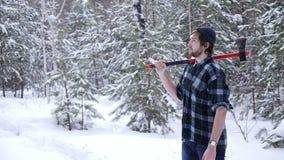 站立与他的轴的伐木工人在森林,轻的漏出围拢他 股票录像