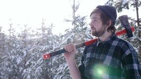 站立与他的轴的伐木工人在森林,轻的漏出围拢他 影视素材