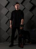 站立与黑短毛猎犬狗的肌肉人 免版税库存图片