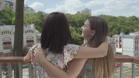 站立两个俏丽的女孩户外一起拥抱和谈话,敬佩美好的都市风景 女朋友谈论 股票录像
