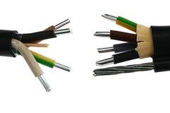 站立两个厚实的铝电力的电缆装置互相反对,一个与在PVC鞘的支持的钢索 免版税库存照片