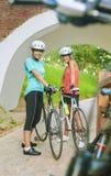 站立两个女性白种人的骑自行车者户外微笑 图库摄影