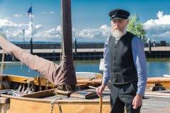 站立为传统渔船的老水手在港口Urk 库存图片